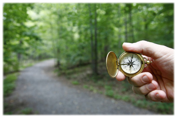 Vintage brass compass close up in hand. Gravel trail curving through woods blurred in background.